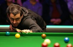Ronnie O'Sullivan sitting at a table with a ball in a room